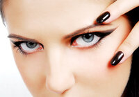Close up of a women's eyes, which feature elaborate black eye liner, with two of her fingers, which are wearing black nail polish, framing her left eye