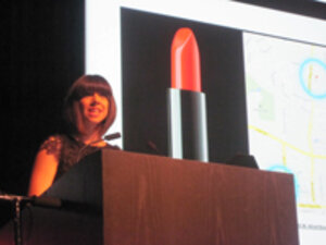 Woman speaking at a podium in front of a presentation slide with lipstick on it
