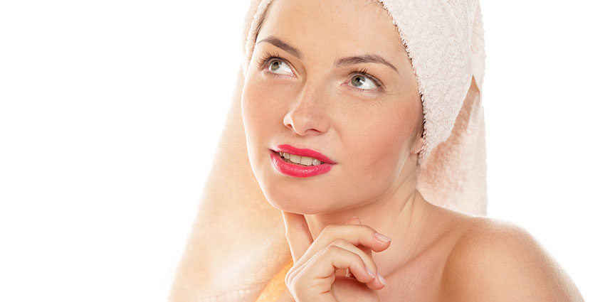 Woman in lipstick and towel thinking