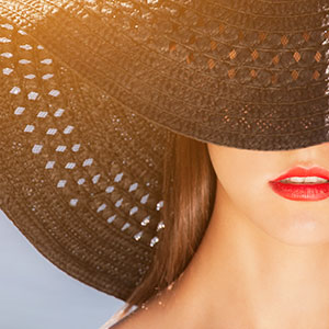 Woman in wide hat on sunny day wearing lipstick