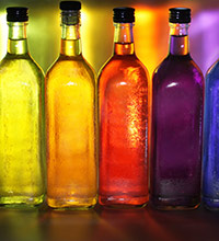 Brightly backlit yellow, orange, red, purple and blue glass bottles