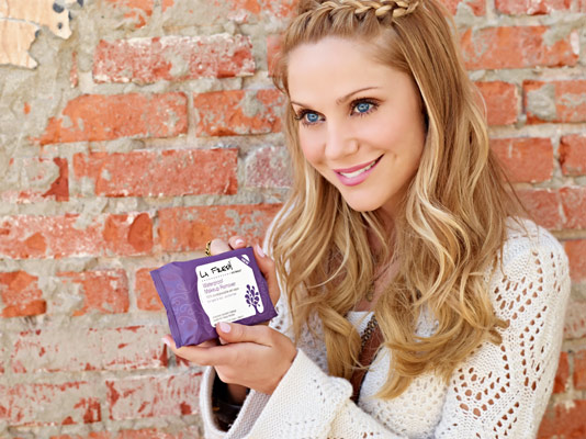 La Fresh brand celebrity spokesperson and actress Virginia Williams holding purple pack of La Fresh makeup remover wipes