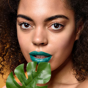 Curly-haired woman with blue lipstick and leaf