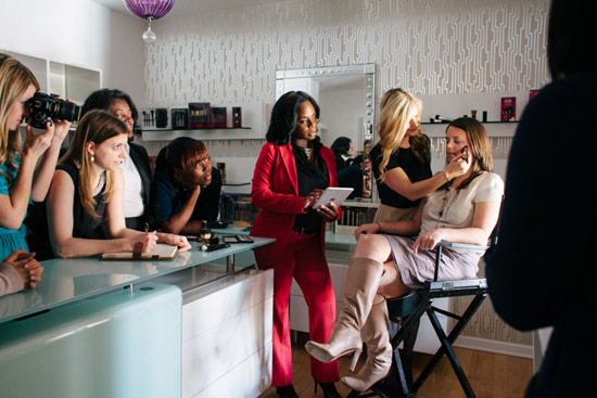 A group of women watch a makeup application demonstration from a professional makeup artist