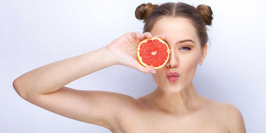 Sassy woman holding grapefruit