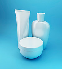 White, label-less beauty products on a blue background