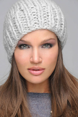 Model with smoky eye makeup wearing a gray knit hat