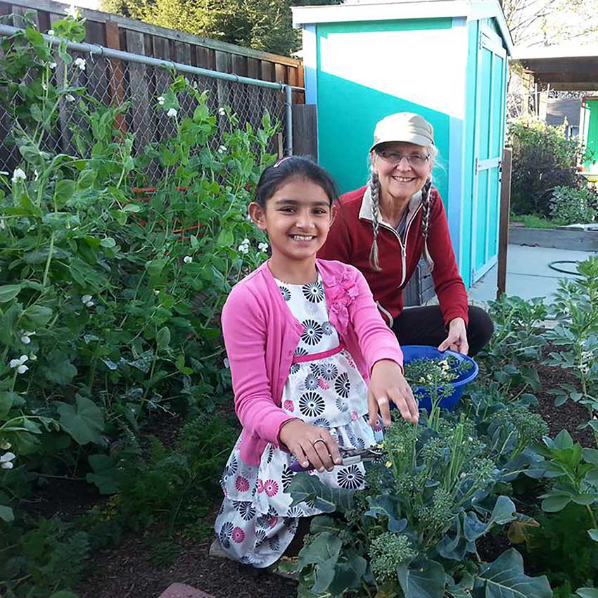 Young girl gardening with teacher