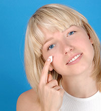 Girl with a tilted head applying skin cream to her cheek