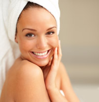 Smiling girl with her hair wrapped in a white towel, touching her face