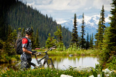 Man on a bicycle, looking at a scenic forest, lake and mountain view